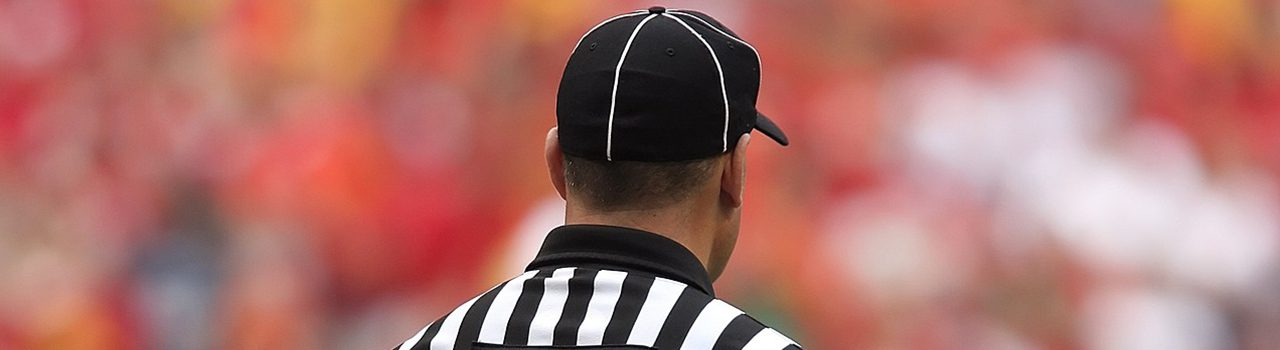 back of a referee wearing a striped black and white shirt and cap